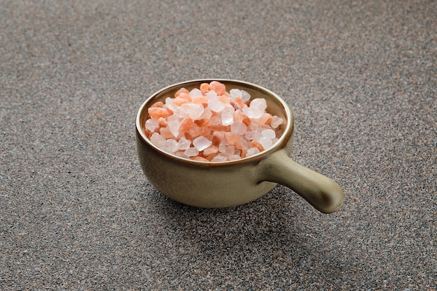 Sal do himalaia rosa em uma tigela de cerâmica na superfície de pedra