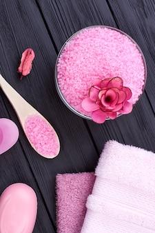 Sal do himalaia rosa plano de vista superior para tratamento de spa. fundo de mesa de madeira preto.