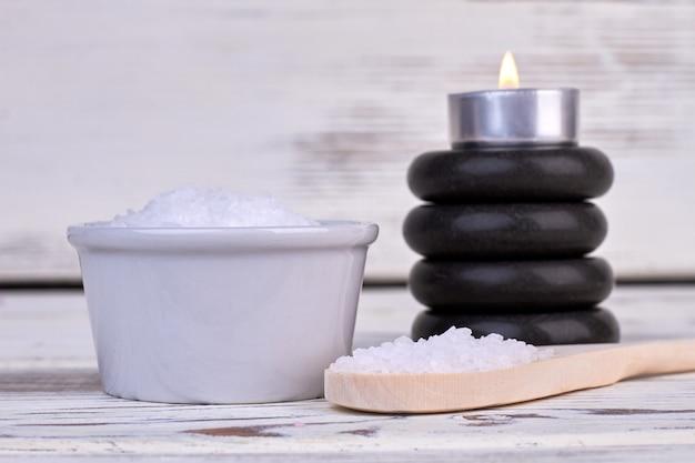 Sal do mar branco com pilha de pedras e vela acesa