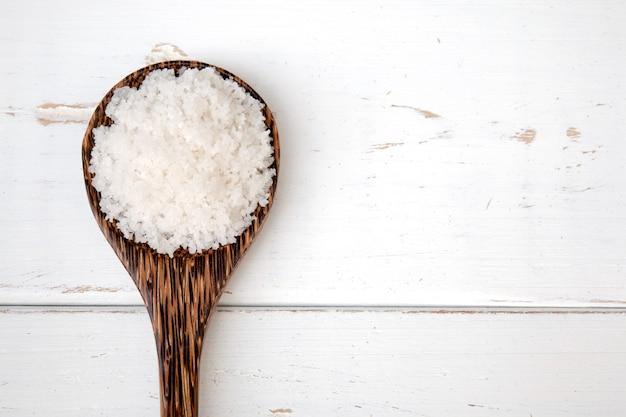 Sal do mar em colher de madeira no fundo de madeira branco