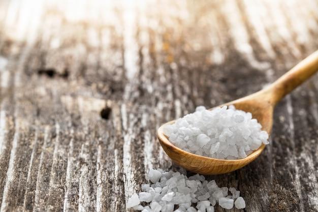 Sal do mar em uma colher na mesa de madeira
