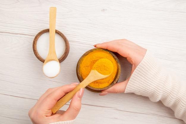 Sal e pimenta de cima dentro de pequenos potes na mesa branca