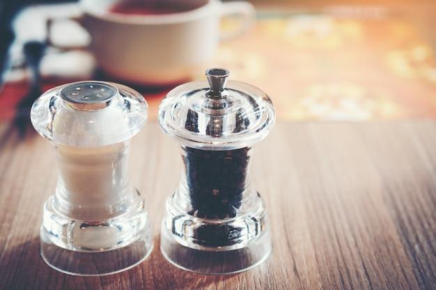 Sal e pimenta na mesa de madeira no restaurante