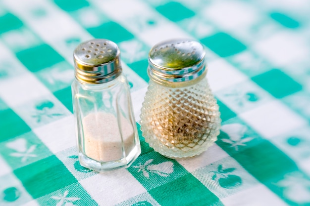 Sal e pimenta shakers em uma toalha xadrez verde