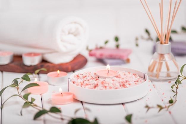 Sal himalaia esfoliante feito à mão. conjunto de produtos de higiene pessoal com velas e toalha branca.