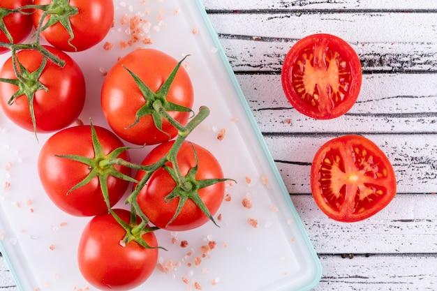 Sal marinho de tomate em tábua plástica branca vista superior na superfície branca