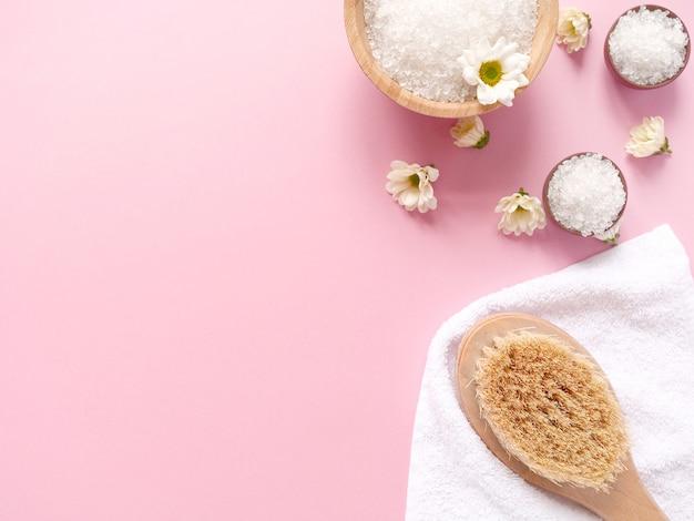 Sal marinho e produtos de banho perto de toalha no fundo rosa