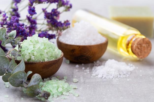 Sal marinho em uma tigela, óleo de aroma em garrafas, bem-estar e flores na superfície cinza e flores na mesa de madeira vintage. foco seletivo.