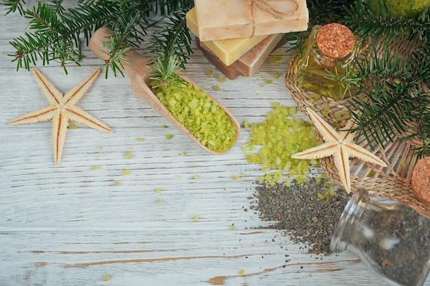 Sal marinho natural e sabonete artesanal com ramo de pinheiro e algas na madeira branca.