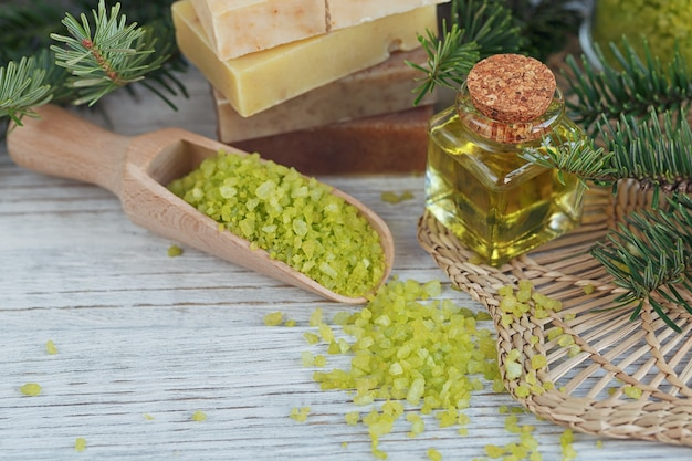 Sal marinho natural e sabonete artesanal com ramo de pinho em madeira branca.