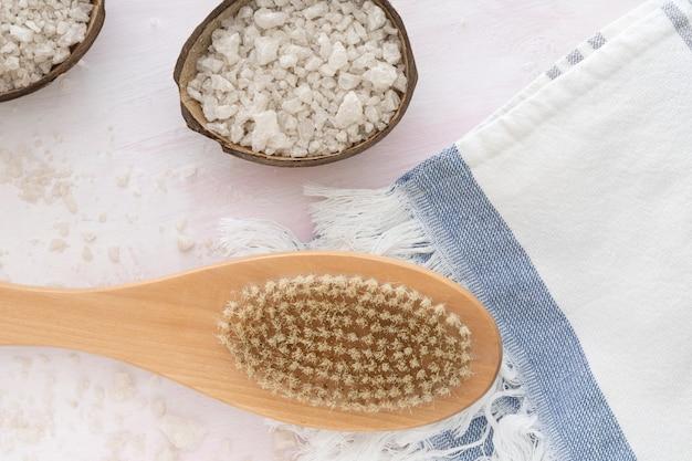 Sal marinho, toalha, escova de massagem de madeira na parede branca