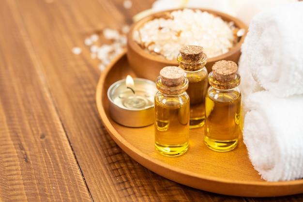 Sal marinho, toalhas, óleo de aroma em garrafas e flores em fundo de madeira vintage.