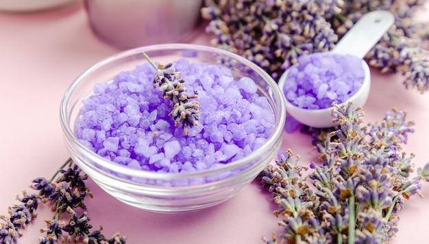 Sal marinho violeta de lavanda com flores de lavanda. produtos de banho lavanda tratamento de aromaterapia em fundo rosa. produtos cosméticos de banho de beleza para spa skincare para relaxar.