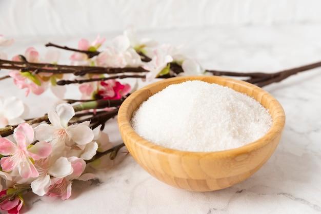 Sal mineral de alto ângulo com flor ao lado
