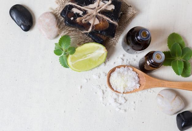 Sal natural do mar e sabão feito a mão com óleo do corpo em um conceito branco dos termas do fundo. top wiev
