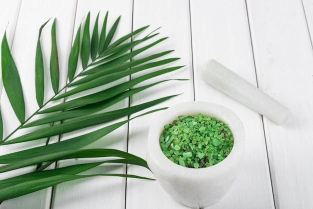 Sal verde de espirulina à base de plantas em almofariz de mármore branco