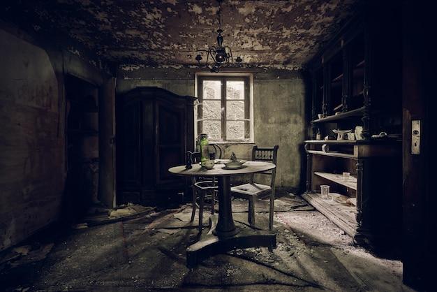 Sala abandonada com uma mesa no meio e prateleiras contra a parede perto da janela