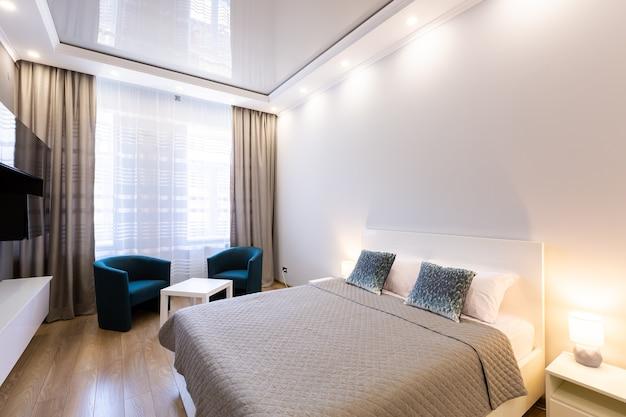 Sala ampla com cama, móveis e tv em estilo moderno