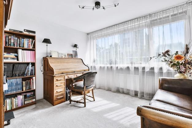 Sala branca iluminada pelo sol com secretária de madeira e poltrona perto da estante e janela com cortina branca