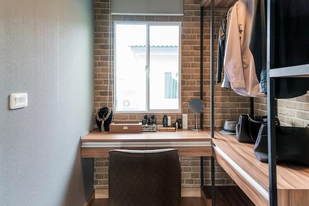 Sala com prateleiras de madeira e vestidos pendurados sob o rack
