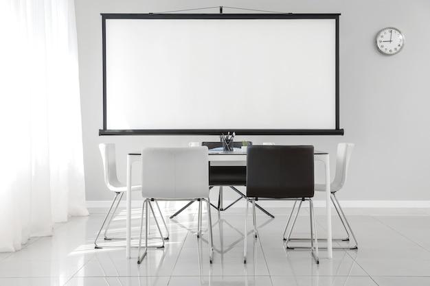 Sala com projetor preparada para conferência em escritório