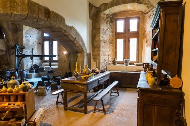 Sala da cozinha vintage no antigo castelo, na europa. arquitectura tradicional europeia, locais famosos para turismo e viagens, interiores de cozinha medieval, pratos e utensílios