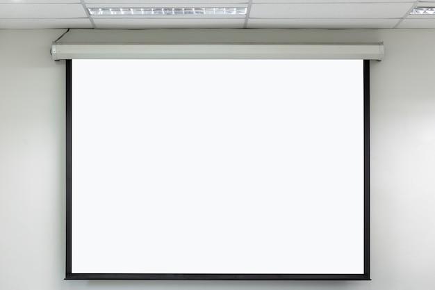 Sala de aula com tela vazia de projetor branco.