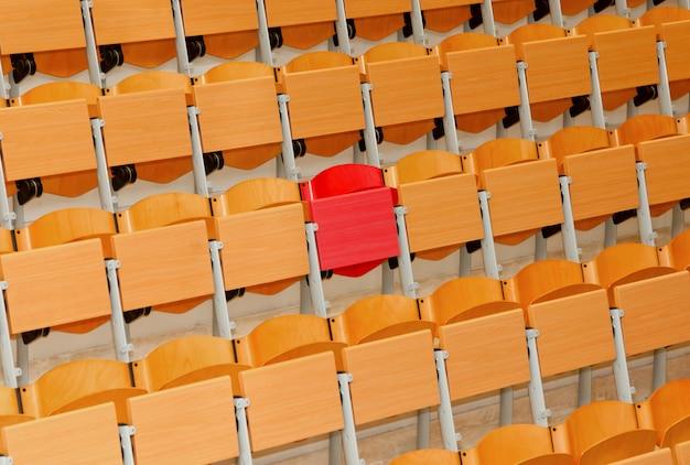 Sala de aula vazia com cadeiras de madeira e uma cadeira vermelha