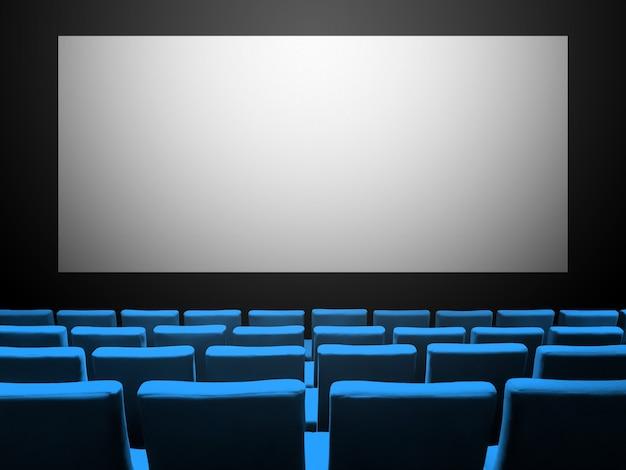 Sala de cinema com poltronas de veludo azul e tela branca e vazia