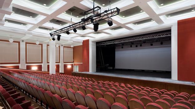 Sala de concertos do teatro com cadeiras novas vermelhas.