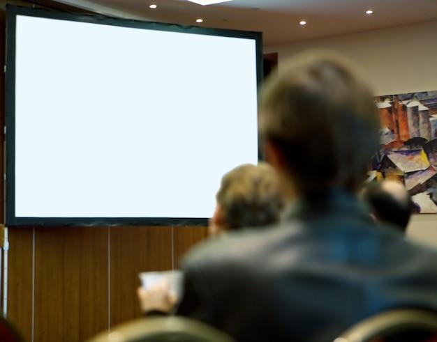 Sala de conferências cheia de pessoas participando do treinamento empresarial.