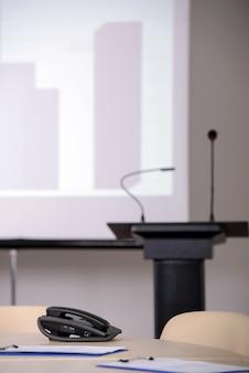 Sala de conferências com tribuna e telas de apresentação.