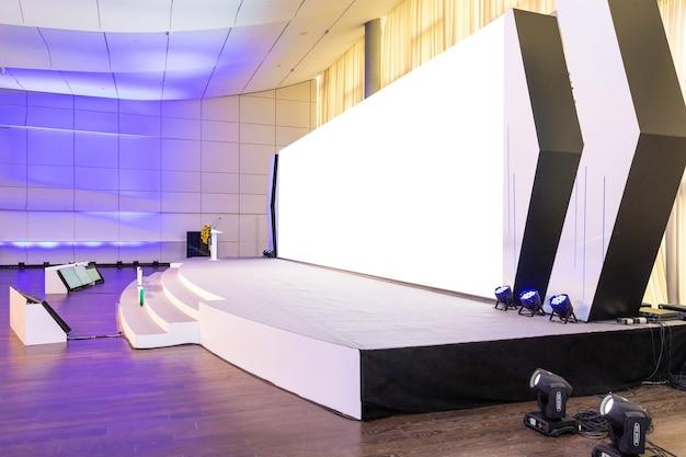 Sala de conferências vazia com tela de projeção branca vazia