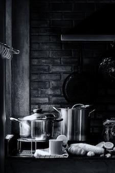 Sala de cozinha com utensílios de cozinha, fogão, exaustor e parede de tijolos com uma xícara de chá de limão com vapor e vapor. conceito da vida do amante do cozinheiro chefe ou do cozinheiro. imagem preto e branca retrô.