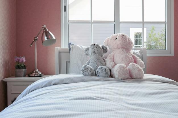 Sala de crianças com bonecas e travesseiros na cama e mesa de cabeceira