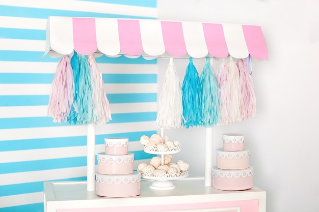Sala de crianças com faixa azul. zona de fotos de barraca de doces com grandes biscoitos, doces e marshmallows. carrinho com sorvete. quarto decorado para aniversário. carrinho com barra de chocolate.