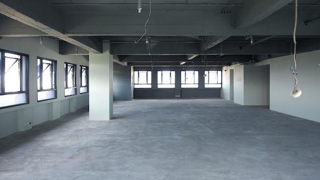 Sala de escritório abandonada que tem chão e parede velhos e sujos e tem janela ao redor e fotos internas.