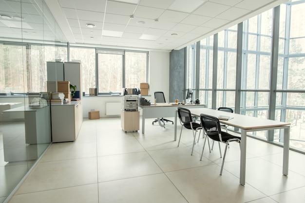 Sala de escritório moderna com janela panorâmica mobiliada com mesas e cadeiras, escritório vazio