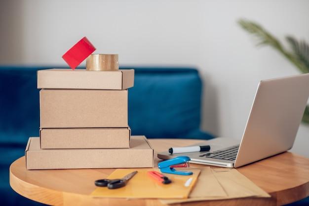 Sala de escritório moderna com um laptop e vários materiais de embalagem