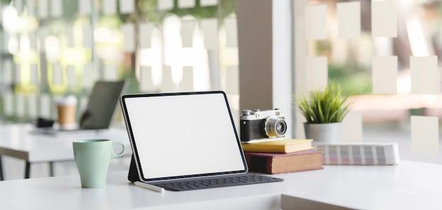 Sala de escritório moderno com tablet de tela em branco, câmera e material de escritório