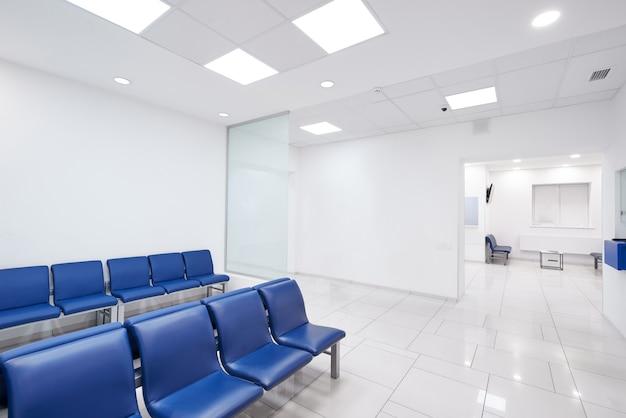 Sala de espera do hospital com cadeiras vazias.