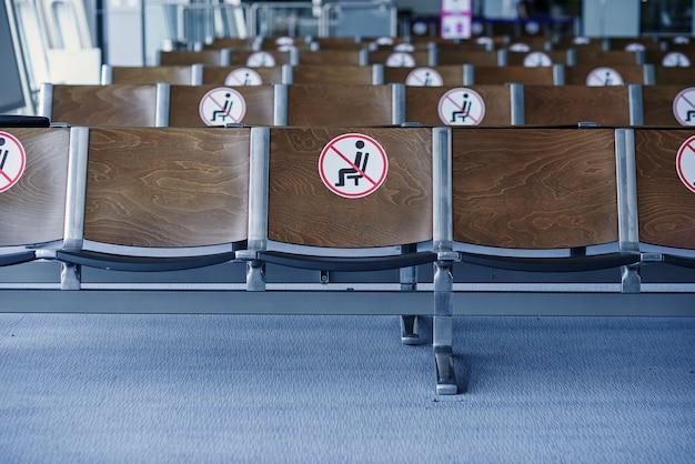 Sala de espera vazia no aeroporto moderno com métodos preventivos proibidos de sentar as cadeiras uma a uma.