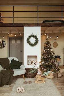 Sala de estar aconchegante e aconchegante decorada com árvore de natal com presentes, moldura de grinalda, lareira, sofá, carpete.
