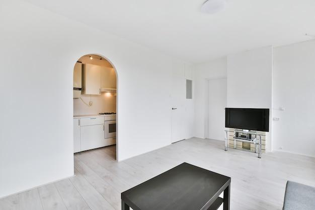 Sala de estar branca com tv e mesa de centro preta e porta em arco para a pequena cozinha