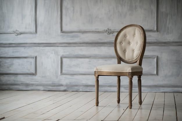 Sala de estar com cadeira leve à moda antiga em elementos de rocococo de molduras de estuque de baixo-relevo de design de parede branca de luxo