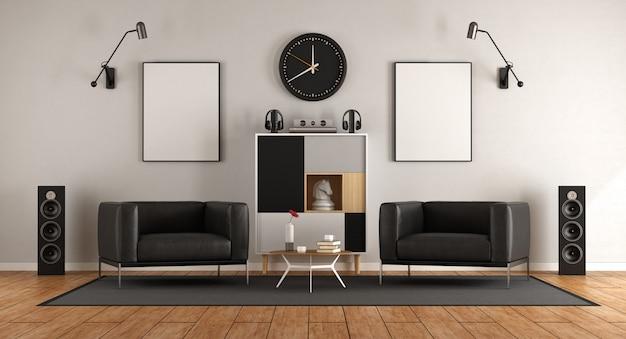 Sala de estar com duas poltronas pretas e equipamento de áudio