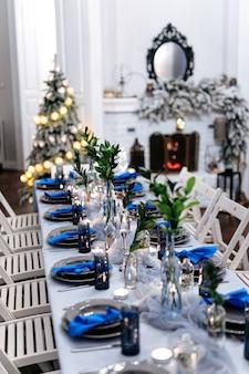 Sala de estar com mesa servida, lareira e árvore de natal