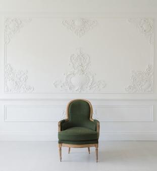 Sala de estar com poltrona verde elegante e antiga em elementos de rocococo de molduras de estuque de baixo-relevo de design de parede branca de luxo