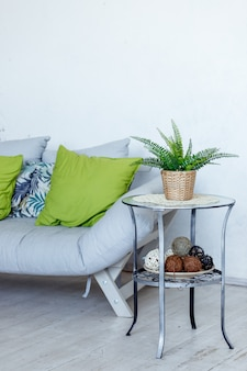 Sala de estar com sofá cinza, almofadas decorativas verdes e planta. interior elegante do quarto em estilo eco com sofá macio e planta verde em pote. copie o espaço. interior do apartamento loft com sofá