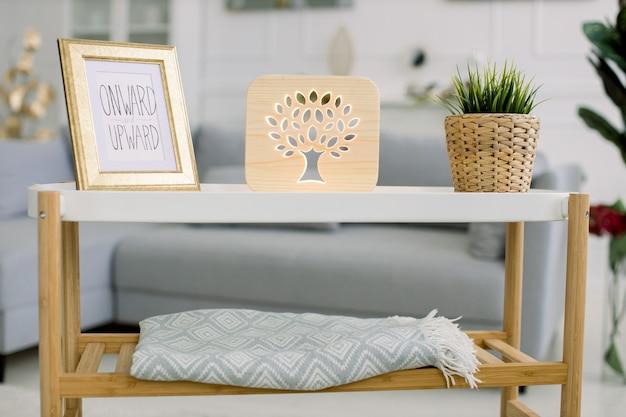 Sala de estar com sofá cinza e mesa de centro moderna com moldura, lâmpada decorativa de madeira com imagem de árvore e planta verde em vaso de vime.